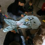 Kinder versammelt um ein Tuch in Fischform mit Bildern von Angstmotiven