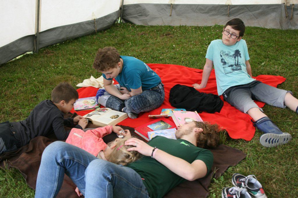 Jugendliche liegen auf der Wiese und entspannen